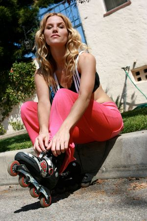 A pretty girl ties the laces on her rollerblades photo