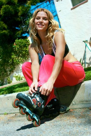 A pretty girl ties the laces on her rollerblades