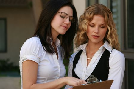 Beautiful business woman looks over documents with her assistant Stock Photo - 4716092
