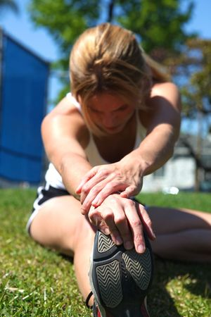 Athletic girl stretching at the track getting ready to run photo