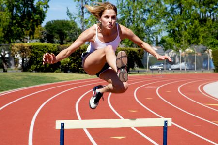 Athletic girl hurdling at the track photo