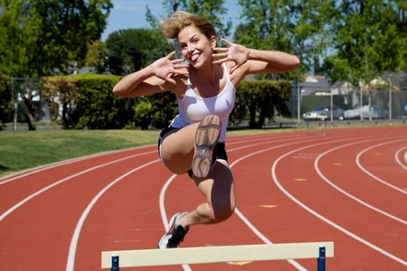 Athletic girl hurdling at the track Stock Photo