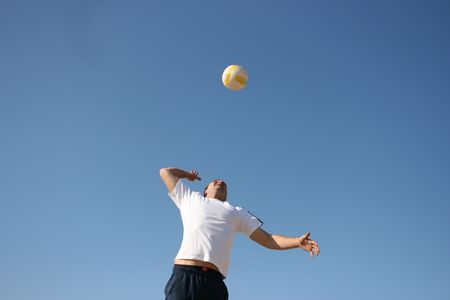 Attractive man serving a volleyball at beach Stock Photo - 4739761