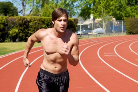 A man jogging at the track with his shirt off