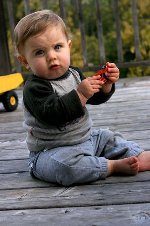 A cute little boy plays with a toy photo