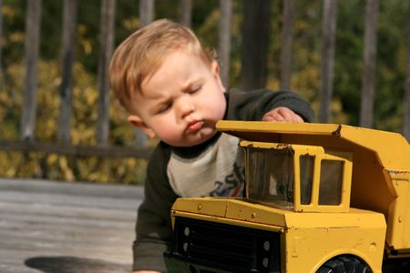 A cute little boy plays with a yellow truck photo