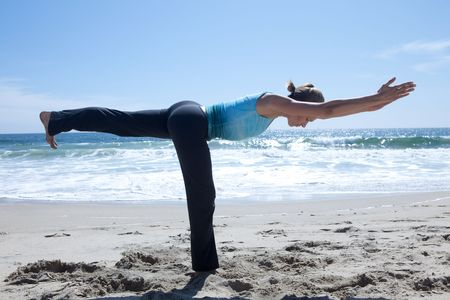 Woman Doing Yoga at the Beach Stock Photo
