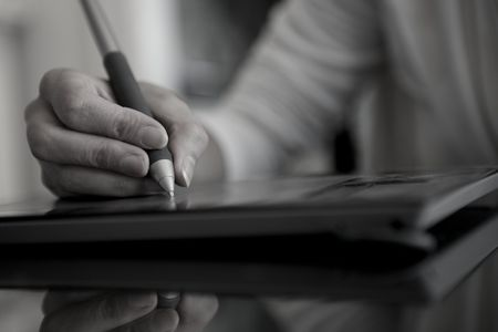 desaturated: Isolated hand sketching onto draw pad with color desaturated Stock Photo