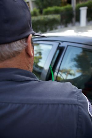 A man in uniform breaking into an automobile with a slim jim photo