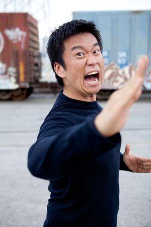 An angry asian man performing karate moves toward the camera