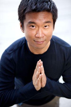 selected: An angry asian man performing karate moves toward the camera