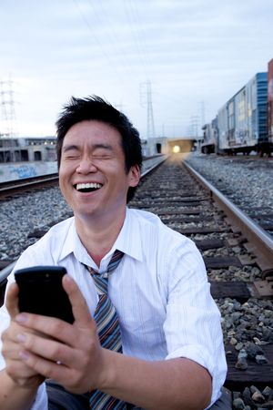 An Asian man sitting on the train tracks making a call photo