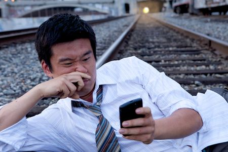 selected: An Asian man sitting on the train tracks making a call