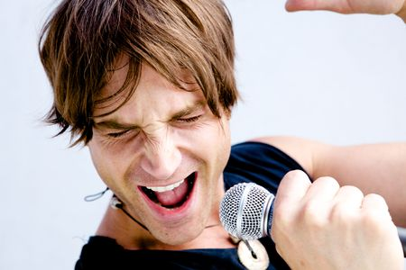 A Rock Star Jamming out with a microphone Stock Photo