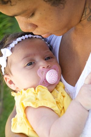 An African American Mother holder her child with a pacifier photo
