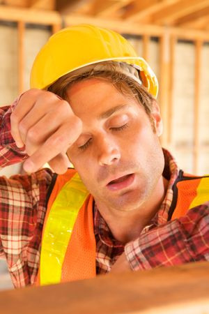 A tired construction worker wiped his head photo