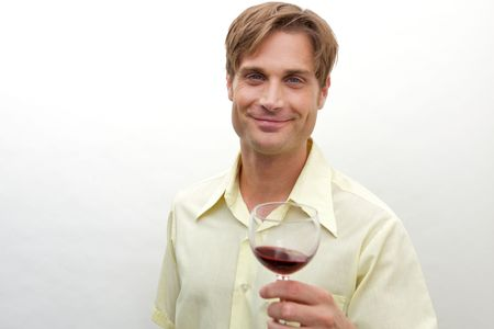 A young man toasting with a glass toward camera Stock Photo
