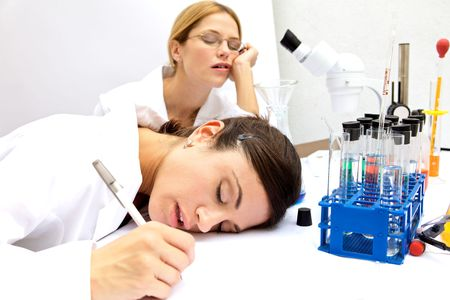 Two female scientists Asleep in a lab photo