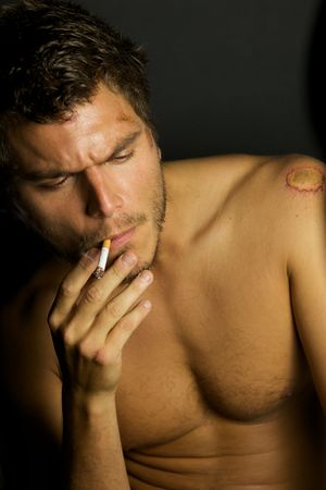 A portrait of a young sexy man smoking a cigarette Stock Photo