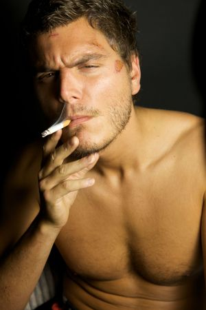 A portrait of a young sexy man smoking a cigarette photo