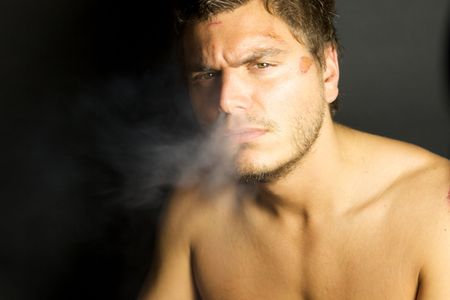 A portrait of a young sexy man smoking a cigarette Imagens