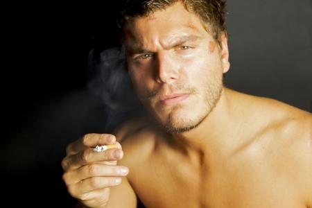 A portrait of a young sexy man smoking a cigarette Standard-Bild