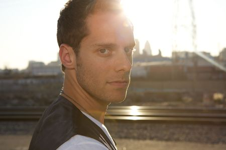An attractive young man backlit with tracks