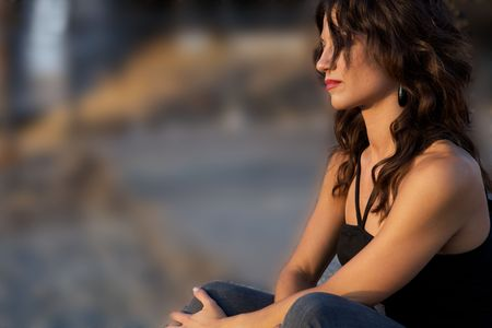 A young sad woman sitting by herself looking away