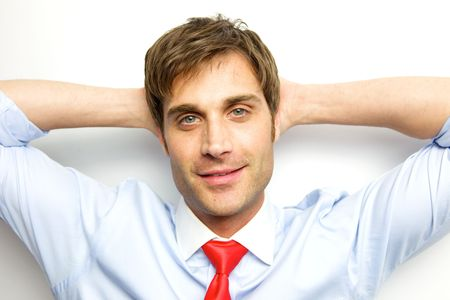Young Businessman sitting back with his arms behind his head photo