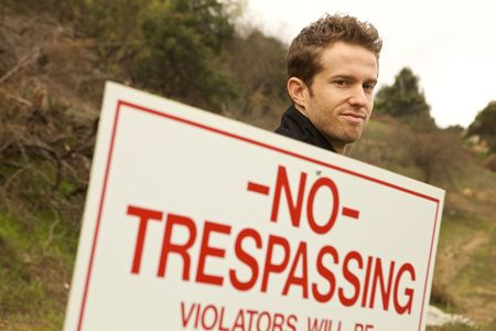 A Man Passing No Trespassing Sign marked and illegal action Stock Photo - 6387537