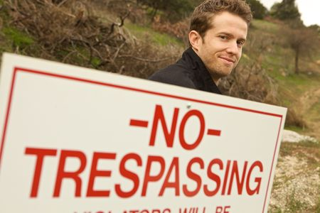 A Man Passing No Trespassing Sign marked and illegal action photo
