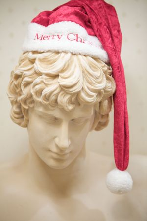 hat new year s eve: A Marble Greek Statue With Santa Hat looking down Stock Photo