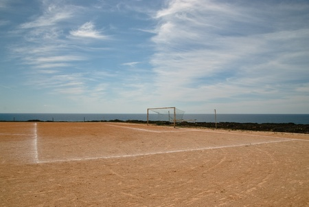 level playing field: An old soccer  football  field with dirt surface, located by the seashore