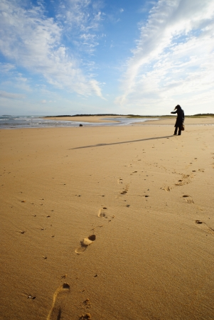 A woman walking on the beach, leaving footprints on the sand  photo