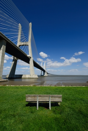 Shot of a bench on a park, with the Vasco da Gama bridge as background  photo