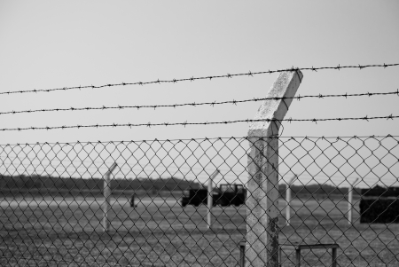 A shot of a barbed wire fence, in a military environmente, taken in black and white. photo
