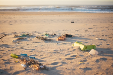 Various pieces of trash scattered around on a beach. The ocean can be seen in the background, blurred. photo