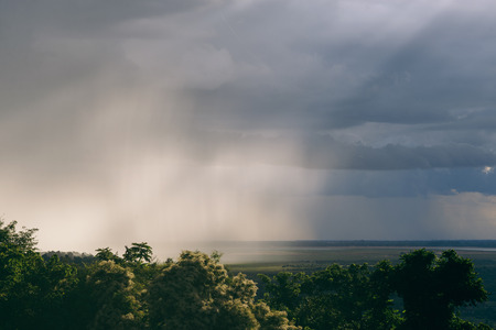 approaches: An intense rain storm approaches its rain clouds intercepted by the sunrays of the sunset making for a fantastic view. Registered from a mountain top in the midst of the jungle in Cambodia.
