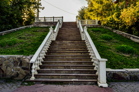 Stairs up in the Park with stone steps and white railings