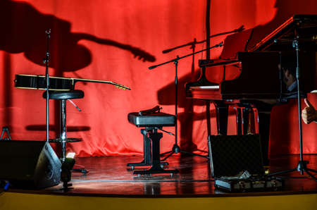 A piano and a guitar on stage before the concert unusual lighting conditions Reklamní fotografie