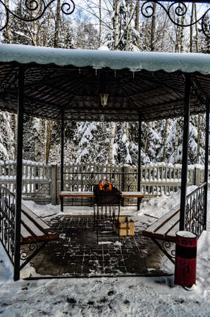 Barbecue in the gazebo under the canopy in winter with fire
