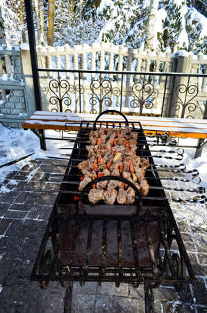 Meat is fried on a brazier in the winter in good weather