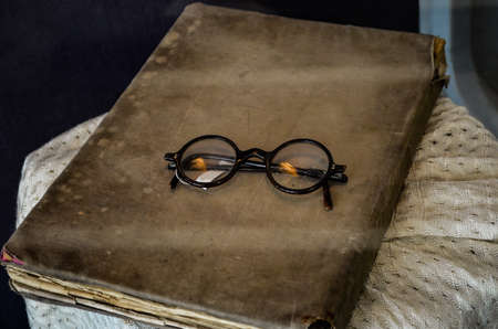 Vintage glasses lie on the old book cover on the tablecloth Reklamní fotografie