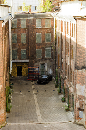 Vintage courtyard with vintage cars Sunny day brick houses
