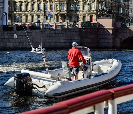 Boat with motor on the city channel swims with one person