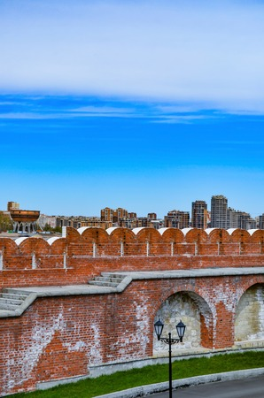 Behind the brick wall is a city with large buildings, a bright, colorful picture.