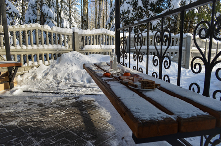 Alcohol and food on the bench in the gazebo on a Sunny winter day