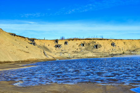 Dugouts on the shore of an abandoned sand pond blue water Reklamní fotografie