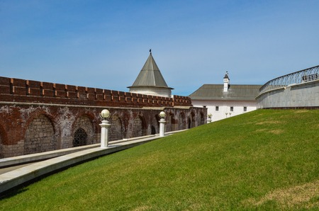 Old brick wall of the Kremlin on the background of the lawn
