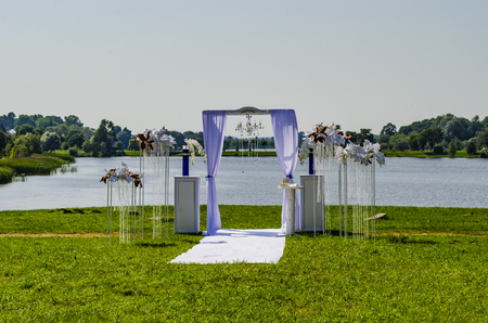 Wedding arch on a glade near the lake in clear weather Reklamní fotografie